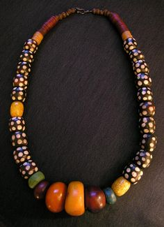"Piece of antique Moroccan amber, polka dot bone beads from Kenya, horn beads from Togo, antique hebron beads made from Dead Sea salts and sand, very old African bronze bicones and vulcanite heishi, and some crackled ""African amber"" Bakelite beads. The oxidized sterling silver hook and eye clasp was handmade in Sri Lanka."