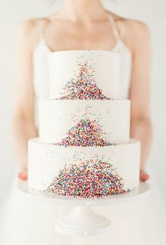 Three-Tiered Wedding Cake with Rainbow Sprinkles. Three classic white tiers get gussied up with a bold and bright dash of rainbow-hued sprinkles.