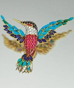 GEM-SET AND DIAMOND BROOCH, VAN CLEEF & ARPELS, CIRCA 1970 Designed as a humming bird in flight, its head and body pavé-set with circular-cut sapphires, rubies and brilliant-cut diamonds, the feathers set with marquise-shaped turquoise, sapphires and brilliant-cut diamonds, mounted in yellow gold and platinum,