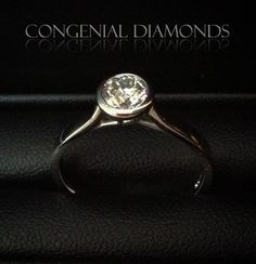 Fabulous diamond engagement ring with stunning crossover detail underneath the rubover setting -