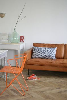 Brown leather sofa | Orange chair | Living room interior inspiration