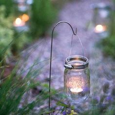 Canning jars with tea lights create a sparkling entrance for an outdoor gathering. More ideas on garden lighting: http://www.midwestliving.com/garden/ideas/19-ideas-for-outdoor-lighting/