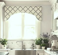 The window valance over this kitchen sink has a nice curve shape, it compliments the stone and marble backsplash. Gray and white are always popular color tones.