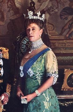 Queen Mary Wearing the Cullinan Diamonds (by Frédéric Bisson) - Queen Mary (l. 1876-1953), consort of George V of England (r. 1910-1936), wearing four of the famed Cullinan diamonds. She is wearing Cullinan I and Cullinan II on her sash and Cullinan III and Cullinan IV from her necklace. Detail of a photo taken 1911-14.