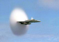 FA-18 Hornet met supersonische snelheid. De wolk ontstaat door condensatie in de ijlere en koudere lucht achter het vliegtuig.