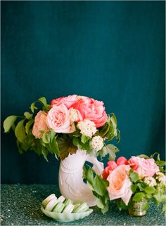 Color palette: coral peonies and pink roses pop against a rich teal backdrop.