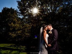 A sunstar appears through the trees as the bride and groom embrace.