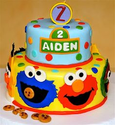 sesame street cake--love the bright yellow bottom but would rather have buttercream icing--I like how the fondant character faces stand out against the yellow (layers would also look good in plain white, then all the colors would really pop!)