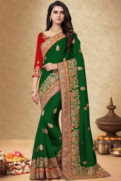 Dark Green silk saree with red silk blouse, embellished with dori work, resham work and sequins work. Saree with Round Neck, Quarter Sleeve. It comes with unstitch blouse, it can be stitched 32 to 58 sizes. #dark green #silk #saree #blouse #Andaazfashion #UK