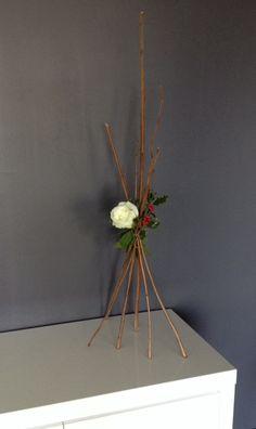 Une composition florale idéale pour un buffet de Noël. Une imitation bougie, à pile bien entendu, posé dans le centre ou au pied de la décoration et l'effet chic et romantique est assuré. Une rose dans un tube à essais, bambous, houx, laurier sauce, sapin et liens raffia pour assembler le tout et le tour est joué !