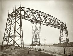"Circa 1905. ""Aerial bridge. Duluth, Minnesota."" Suspended Car Transfer over the Duluth Ship Canal. The gondola could carry 60 tons of cargo across the 300-foot channel with minimal obstruction of the shipping lane. After modification for service as a vertical lift, the span became known as the Aerial Lift Bridge. 8x10 dry plate glass negative, Detroit Publishing Company."