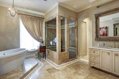 414 Cowan Dr. Alternate view of the master bath shows walk-in shower with travertine surround, stylish accent tiles, two shower heads and frameless shower door. Separate pedestal tub and gorgeous chandelier. Large window provides natural light.  Bernstein Realty, Houston Real Estate.