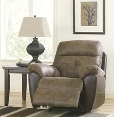 """The Hewson Rocker Recliner With a rich two-tone style to the faux leather upholstery fabric surrounding the shaped padded arms and bustle back design adorned with stitched and tufted detailing, the """"Hewson-Earth"""" upholstery sectional offers both comfort and style to help create the ultimate relaxing living area."""