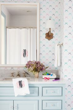 Andrew Howard Interior Design   Pretty shade of blue on the cabinets. Cute bow wallpaper perfect for a child's bathroom.