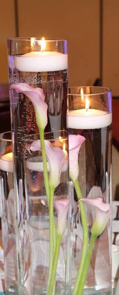 Calla lilies with a hint of pink submerged in water in glass cylinders with floating candles grouped together make very pretty centerpieces.