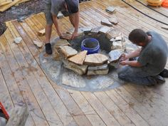Craftsmen constructing a natural stone fire pit on wooden deck with stone inlay. www.southernlivingoutdoors.com