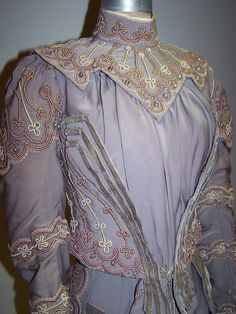 Worn by First Lady Ida McKinley: Grey silk crepe two-piece gown trimmed in pale rose and off-white cording, small pearls, and narrow bands of grey velvet.