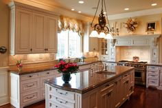 Richly designed white kitchen with cabinet back-lighting, ornate island with sink and dark wood flooring