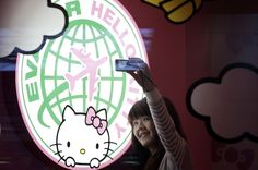 A passenger takes a self-  portrait with an Eva Airlines Hello Kitty - themed light box.