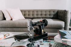 Atop the coffee table sits a Vintage Singer Featherweight Sewing Machine.