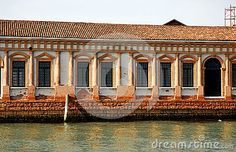 Photo made in the island of Murano in Venice in Italy. In the image taken from the lagoon you see the wall, brick and wet from the water, an old building that was formerly a glassworks. In the low-rise building wall there are many old folks and a neoclassical door.