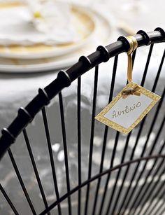 O cartão de lugar não precisa ficar apenas sobre a mesa. Aqui, foi amarrado no encosto da cadeira