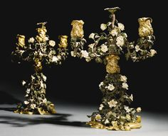 A PAIR OF LOUIS XV GILT-BRONZE, TÔLE AND SOFT-PASTE PORCELAIN THREE-LIGHT CANDELABRA, FRANCE, CIRCA 1745, each with shaped scrolling rockwork base, issuing an elaborate naturalistic foliated tôle stem adorned with white and coloured porcelain flowers topped by grapevine-cast bronze nozzle issuing removable tôle flower decorated triple candle-arms, ending on cast-bronze nozzles