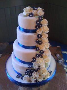 Cascading flowers - Fondant covered wedding cake with cream colored handmade roses and sapphire blue blossoms cascading down. The bride's sapphire engagement ring was the inspiration.