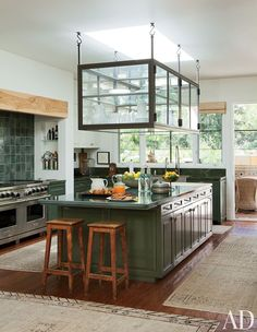Ellen DeGeneres and Portia de Rossi created extra storage space in their Beverly Hills kitchen by suspending a glass display above the island