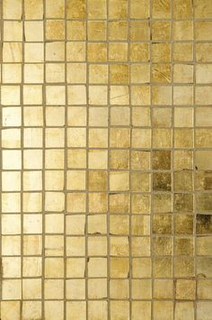 1-inch by 1-inch Davlin gold leaf tiles by Ann Sacks side by side across the entire floor, creating a shimmering luxuriousness in the most unlikely of places.