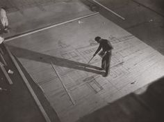 A photograph of a man painting scenery for use in a film set at Ealing Studios, 1939