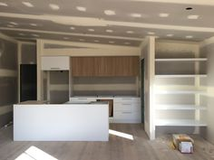 Modern Kitchen with Laminex polar white cabinets and floating shelves + Polytec natural oak revine above counter cabinets   MACAN HOMES PTY LTD by Jacob & Kelli McKenna.