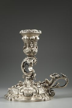 A small, rare silver candlestick in the Renaissance style with a curved handle decorated with openwork foliage and surmounted by a young man lying, playing the flute. A seated Faun...
