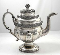 G Eoff Coin Silver Teapot  An enormous American coin silver teapot in superb condition with hand chased decoration on a hand hammered surface. The spout has a duck head terminal and the finial is a basket of flowers. The manufacturer is Garrett Eoff, marked on the pedestal base. Active 1779 to 1845. Holds 10 cups. Small script monogram on one side only.