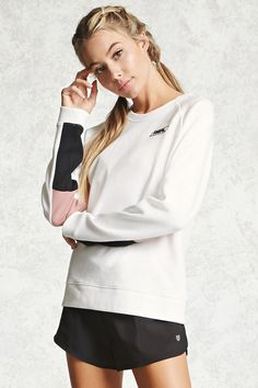 """A knit athletic sweatshirt featuring a """"Real"""" chest patch, long colorblock raglan sleeves, and a round neckline."""