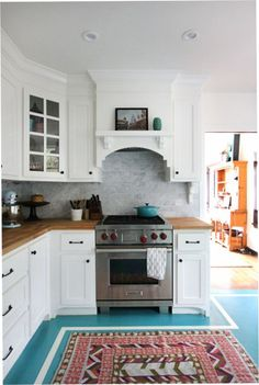 Turquoise floor, butcher block counters, white cabinets. My dream kitchen!