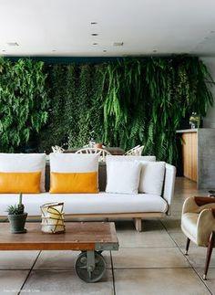 Varanda de apê tem jardim vertical, móveis rústicos e peças de design.