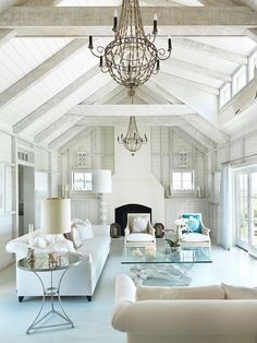 Seaside Residence by Donna Elle Seaside Living - a beautiful blue and white country style living room with gorgeous transitional sofas, glam chandeliers and a driftwood coffee table