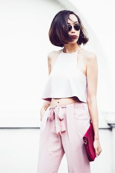 Chriselle Lim wears a crop top, high-waisted pink trousers, a burgundy velvet clutch, and Dior sunglasses