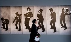 A woman passes an installation showing artist Yoko Ono as part of the exhibition 'The Little Black Jacket' with photos by fashion designer Karl Lagerfeld and former Vogue chief Carine Roitfeld at metro station 'Potsdamer Platz' in Berlin. The exhibition can be seen until mid-December.