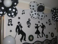Pano na parede com notas musicais, discos de vinil e imagem de pessoas dançando.