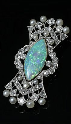 An Edwardian platinum, gold, Australian white opal, natural pearl and diamond brooch, English, circa 1910. 2.1 x 4.3cm.