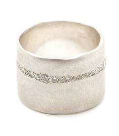 For a bolder look with a touch of glam. This 15mm ultra-wide band sheds an unexpected flash of light with a row of pavé set diamonds. This diamond…