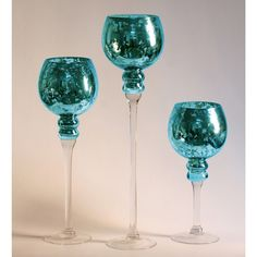 Bring a splash of color and unique style to your home decor with this three-piece stem vase set, crafted of clear and blue mercury glass. The set includes three different sizes of vases for a staggered effect to bring variation and interest to the pieces.