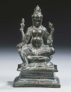a central javanese bronze figure of jambhala   9th/10th century   Seated in lalitasana on a lotus pericarp placed on a rectangular base, four-armed, wearing dhoti, bejewelled, his face with serene expression, tiara in front of his high chignon  14 cm high