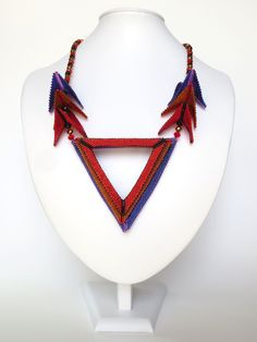 Back to the 80's for this geometrical necklace. All the elements are mobile and playful. Purple and red tones in mid length size.