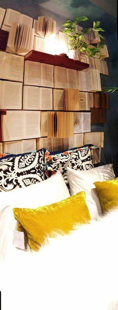 kein richtiges Bücherregal geöffnete Bücher an der Wand über dem Schlafbett