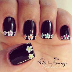 Uñas florales, negras con flores de colores en las puntas.