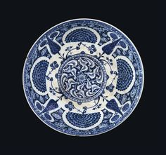 A RARE AND IMPORTANT EARLY IZNIK POTTERY BOWL OTTOMAN TURKEY, CIRCA 1510 Of deep rounded form rising from short foot slightly widening at the base, the white interior decorated in two shades of blue with a central roundel filled with elegant rumi arabesque reserved against a cobalt-blue ground, the roundel with a minor chequered border, the cavetto with usual design of cypress trees growing from grassy tufts which also issue swaying branches from which grow wide semicircular fanned flowers…