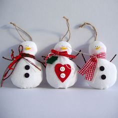 Hanging fabric snowman in white fabric and various embellishments. Materials: fabric, cords, ribbons, buttons,bells Dimensions: 12(h)X8